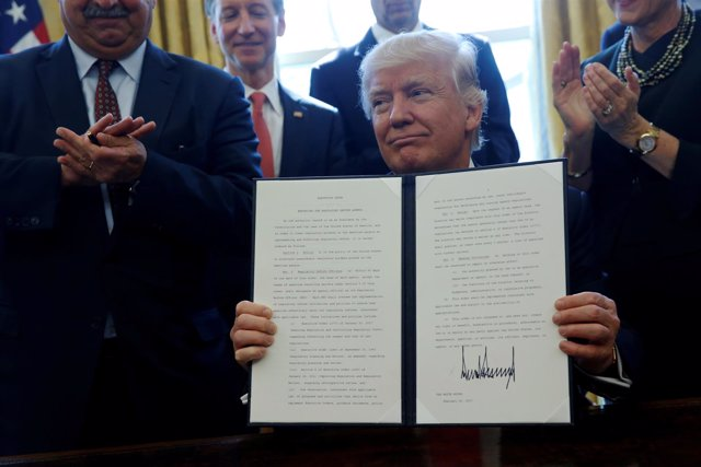Donald Trump firma una orden rodeado de empresarios