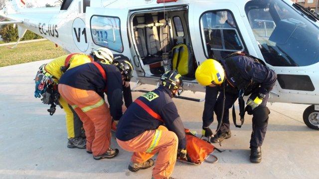 Bomberos y el helicóptero que ha trasladado el cuerpo de la víctima