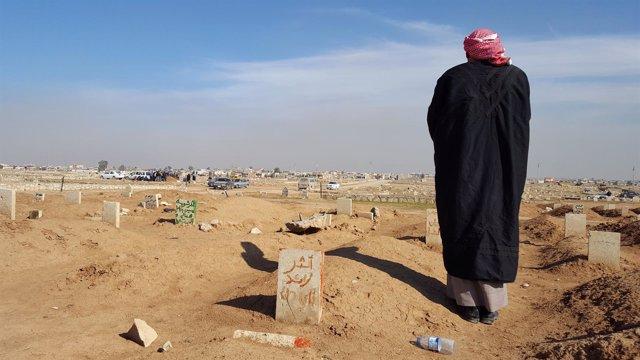 Un padre ante la tumba de su hijo en Mosul, Irak