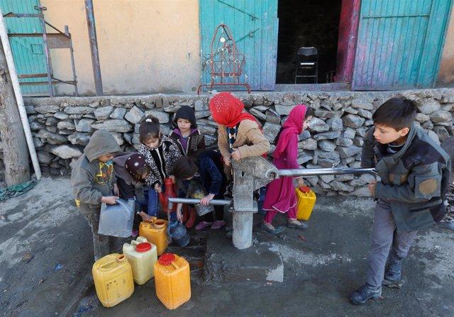 Niños afganos cogen agua de una fuente en Kabul