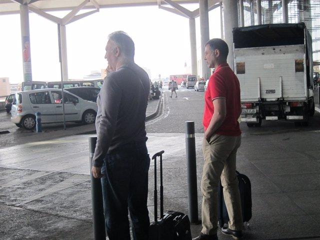 Dos turistas aeropuerto de Málaga viajeros maletas turismo coches