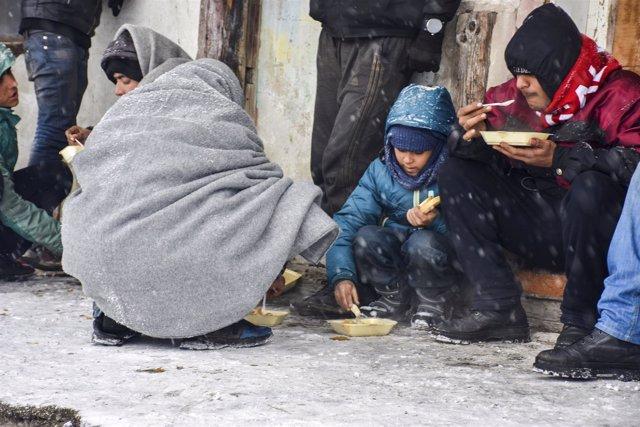 Varios niños comen en un centro de refugiados de Serbia.