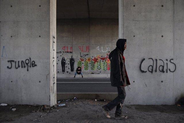 Inmigrante caminando en una zona de campamento improvisado en Calais