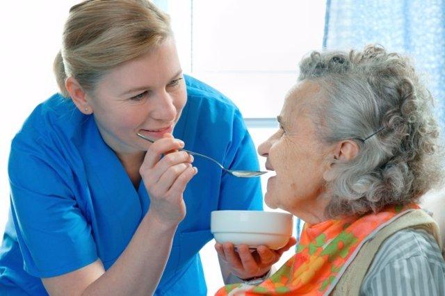 Mujer mayor con demencia o alzheimer comiendo