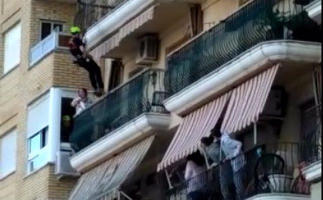 Uno de los bomberos baja hasta el balcón donde está la mujer con dos menores
