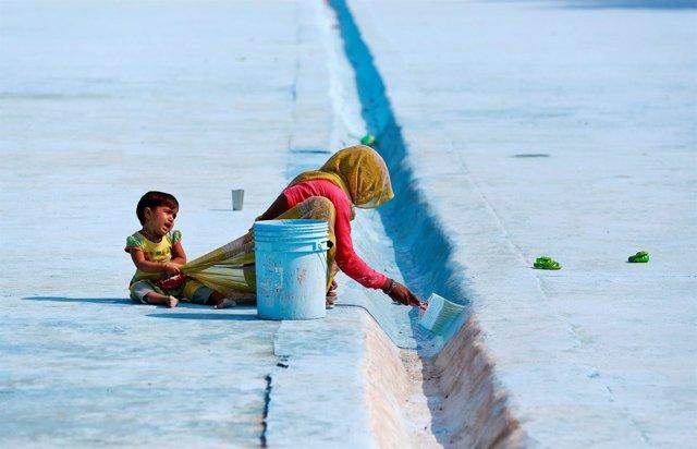 Una mujer pinta el suelo mientras su hijo le tira del vestido