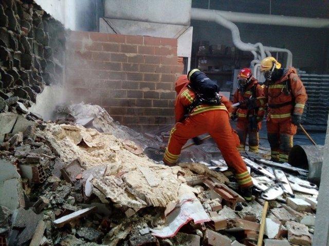 Los bomberos han derribado las paredes de la nave afectada por el fuego