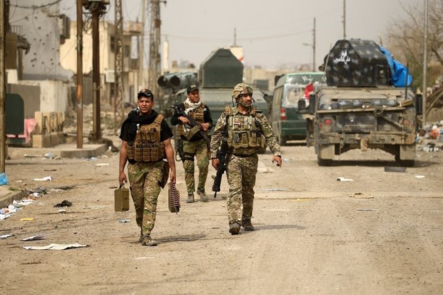 Iraqi rapid response members carry their weapons during a battle against Islamic