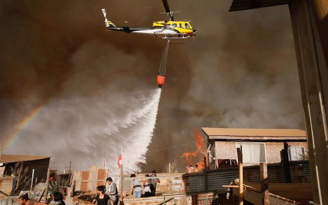 A helicopter makes a water drop to prevent a wildfire from spreading to homes in