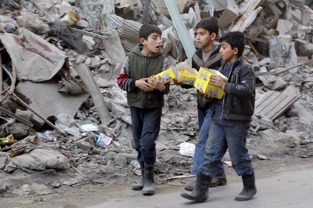 Niños caminan entre escombros en Alepo (Siria)