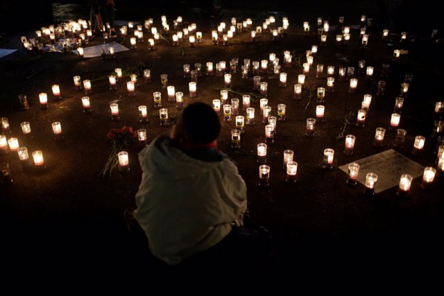 Candles are lit during a vigil for victims after a fire broke out at the Virgen