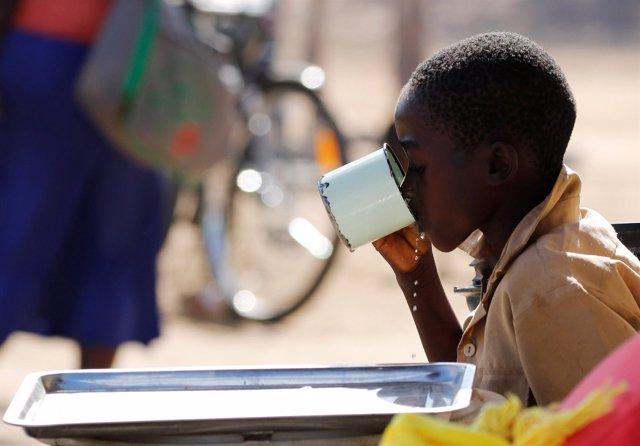 Un niño bebe agua de un vaso en Zimbabwe,