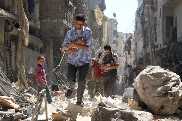 Hombre sirios llevan en brazos a bebés en Alepo