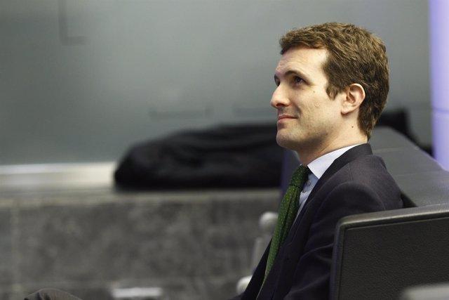 Pablo Casado sigue una rueda de prensa en la sede del PP