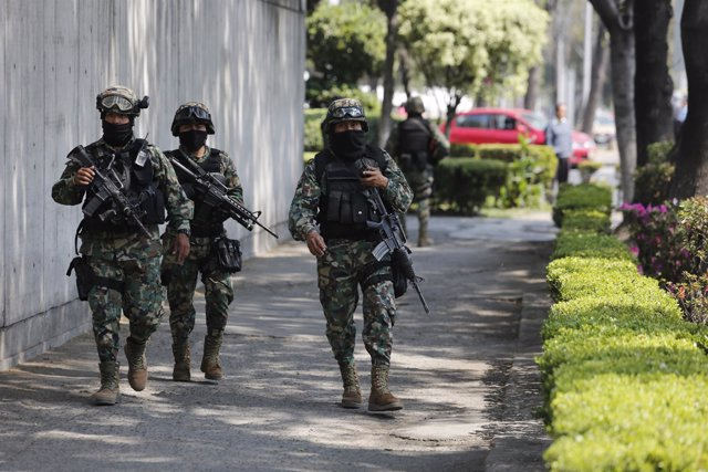 Military personnel walk on a sidewalk after security was stepped up outside the