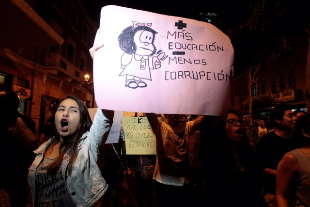 """Protesters hold a sign reading """"More education less corruption"""" to protest again"""