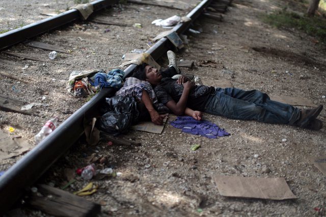 Two migrants from Guatemala sleep on the train tracks in Arriaga August 8, 2014.