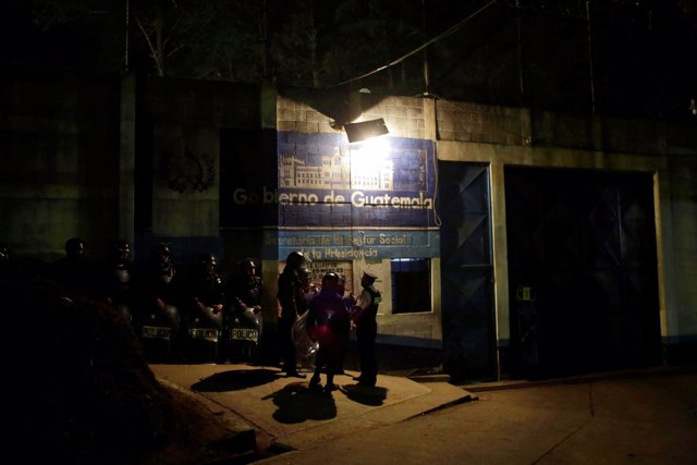 Policemen stand guard after a riot by underage inmates, outside the Correctional