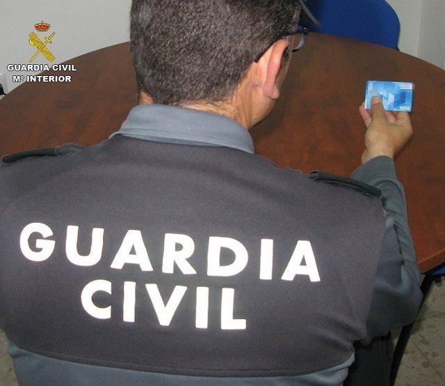 Agente de la Guardia Civil con la tarjeta recuperada.
