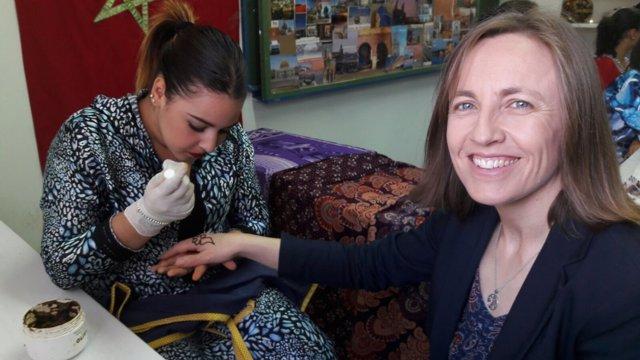 Una alumna hace un tatuaje a la delegada de Educación