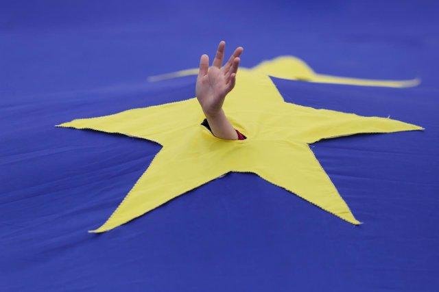 Un niño asoma su mano en una bandera de la UE