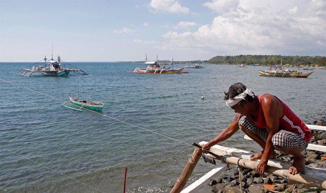 Un pescador repara su barco en Scarborough, en el mar de China Meridional
