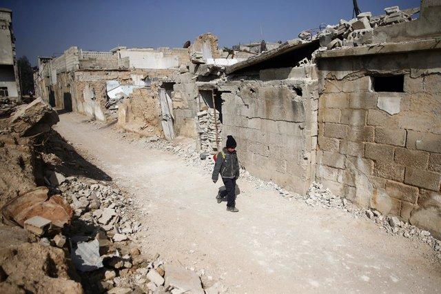 Un niño camina por una calle de Duma