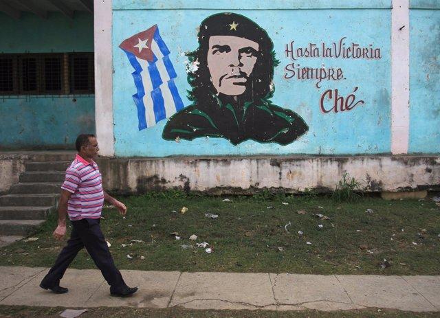 Un hombre pasea por La Habana frente a un mural del Che